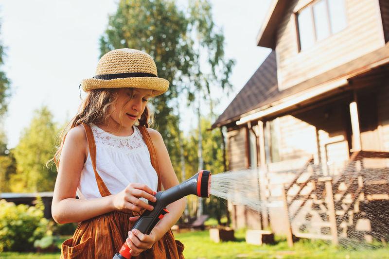 Girl holding garden hose