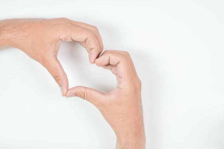 Close-up of hand holding paper over white background