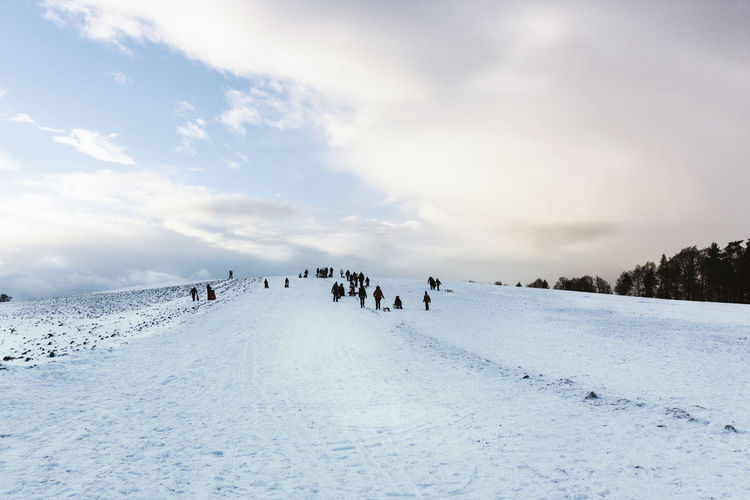 People on snow against sky during winter