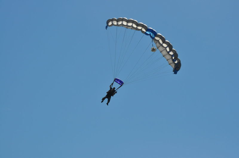 Skydiving with a Clear Blue Sky Background Blue Clear Sky Extreme Sports Flying Jumping Leisure Activity Low Angle View Mid-air Nature One Person Outdoors Parachute People Real People Skydiving Sport