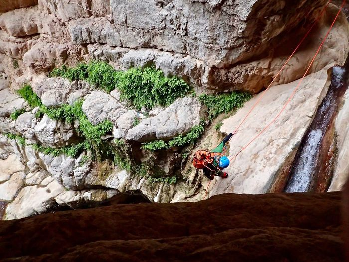 High angle view of man climbing on rock
