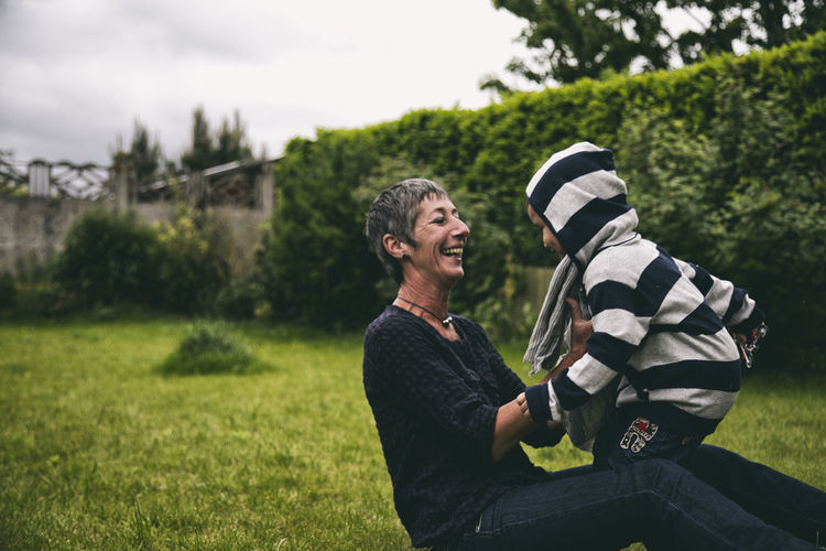 Happy Grandmother With Grandson On Grassy Field