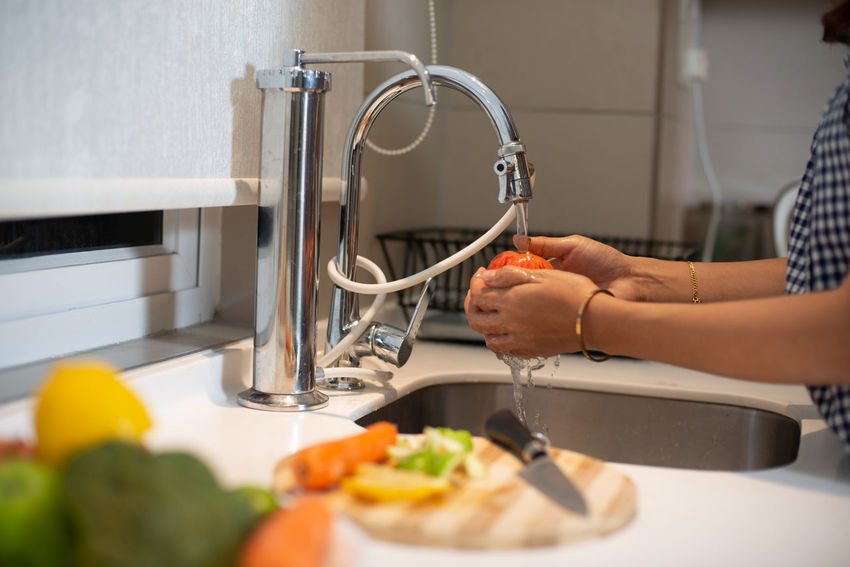 Kitchen Human Hand Indoors  Domestic Room Food And Drink Occupation Hand Human Body Part One Person Food Vegetable Domestic Kitchen Home Real People Preparation  Faucet Holding Healthy Eating Table