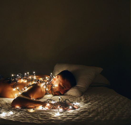 Man sleeping with illuminated string lights on bed at home