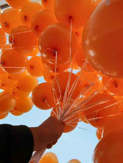 Balloon Orange Color Low Angle View Human Hand Celebration Hand Human Body Part Holding Sky Lifestyles Real People Balloons Fly Away Flying Away Lift Off Lift Weightless Holding On Holding In Hand Ballon Orange Orange Balloon Hold Tight Defying Gravity Large Group Of Objects