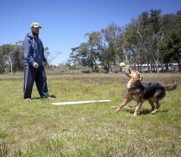Man with dog on field against clear sky