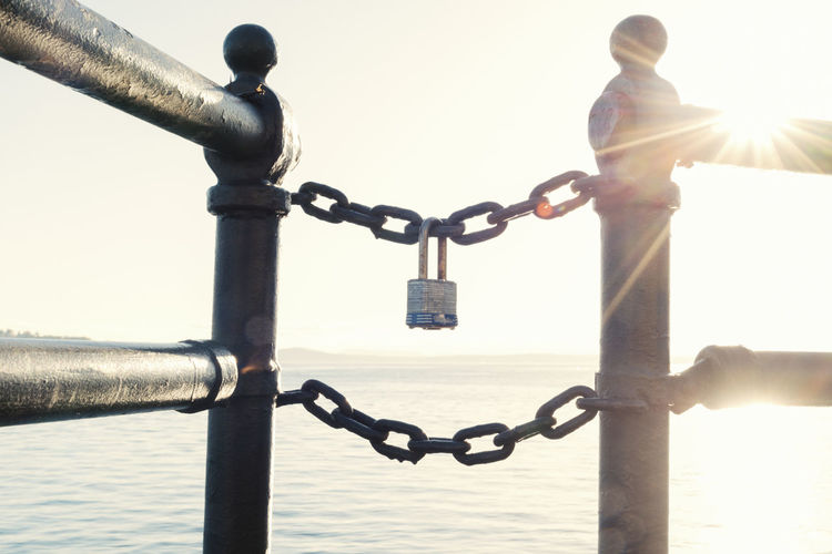 A lock connected to chain link at sunset showing security. Conceptual cryptocurrency digital block chain technology future. Bitcoin Modern Security Sunburst Architecture Banking Barrier Block Chain Boundary Chain Cryptocurrency Day Digital Currency Lens Flare Lock Metal Nature Outdoors Padlock Protection Safety Security Sky Sunlight Water
