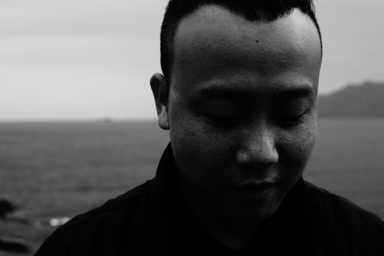 Portrait of young man against sea