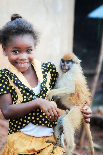 Portrait of cute girl holding monkey
