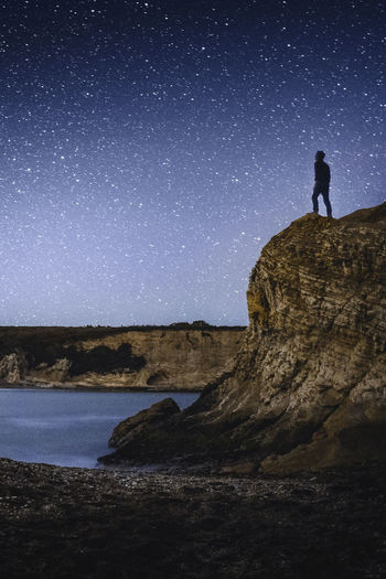 Astronomy Beauty In Nature Full Length Land Leisure Activity Nature Night One Person Outdoors Real People Rock Rock - Object Scenics - Nature Silhouette Sky Solid Space Standing Star - Space Tranquil Scene Tranquility The Traveler - 2018 EyeEm Awards