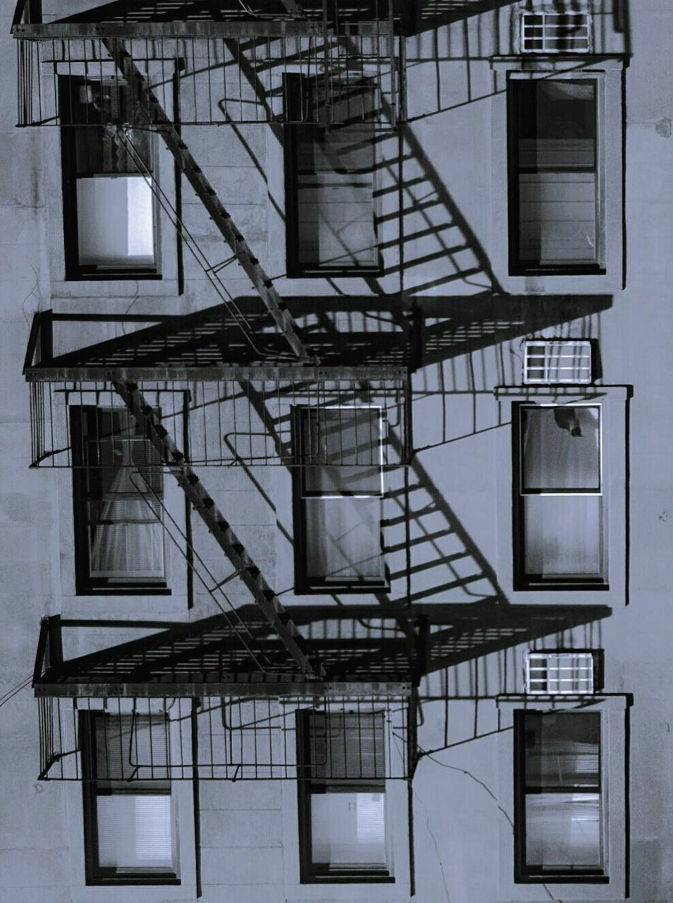 architecture, built structure, building exterior, fire escape, staircase, steps and staircases, no people, accidents and disasters, window, low angle view, building, emergency exit, safety, residential district, outdoors, railing, urgency, day, wall, industry, apartment