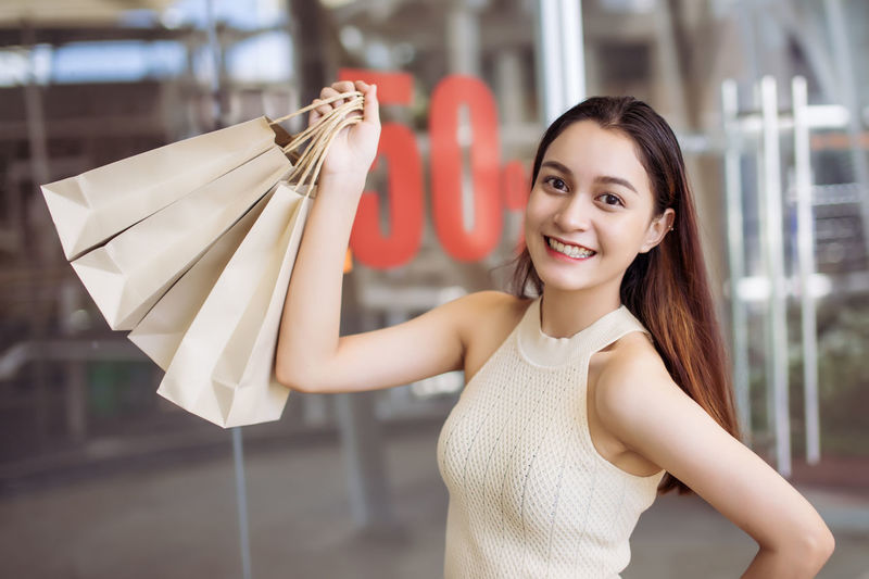 Young women relax and fun with shopping Beautiful Happiness Joyful Market Relaxing Sale Shopping Show Bag Cheerful Discount Happiness Holding Lifestyles Looking At Camera Mall Paper Portrait Relax Shop Smiling Store Women Young Adult Young Women