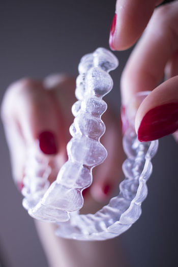 Cropped hand of woman holding artificial teeth