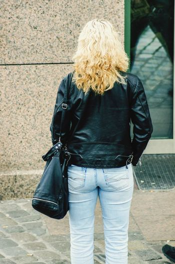 A blonde woman standing on the pavement. Glass Reflection Sunlight Nature_collection EyeEm Best Shots Focus On Foreground Close-up High Angle View Blond Hair Shoe Jeans Wavy Hair Hairstyle Outdoors Real People One Person Rear View Casual Clothing Leisure Activity Lifestyles Women Standing Bag Adult Jacket Three Quarter Length Footpath Holding Street Day