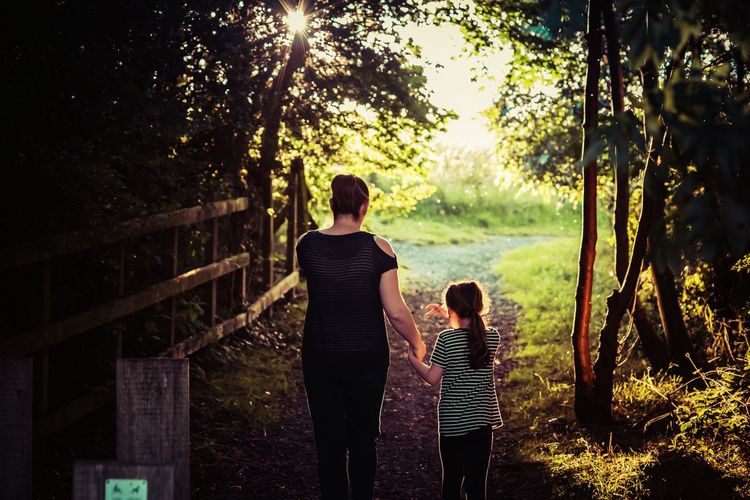 Rear view of mother with daughter on walkway at forest