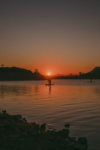 Silhouette person standing in lake against sky during sunset