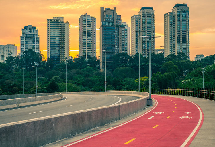 Road by buildings against sky during sunset