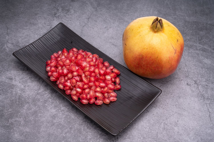 Anticancer Cold Temperature Delicious Drought Resistant Food Fruit Heart Insect Repellent Mature Adult Medicinal Plant Micronutrients Nutrition Pomegranate Pomegranate Seeds Red Red Heart Rich Seeds Supplement Sweet Temperate Zone Tropical Water Food And Drink Healthy Eating Wellbeing Freshness Still Life Indoors  No People High Angle View Table Apple - Fruit Close-up Gray Tray Cutting Board Wood - Material Shape Temptation