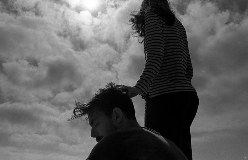 Low angle view of man and woman against cloudy sky