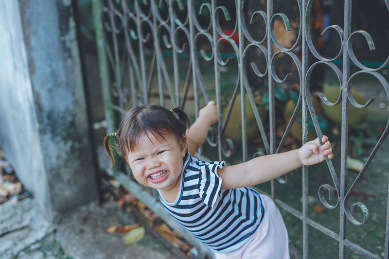 Portrait of cute girl playing on gate