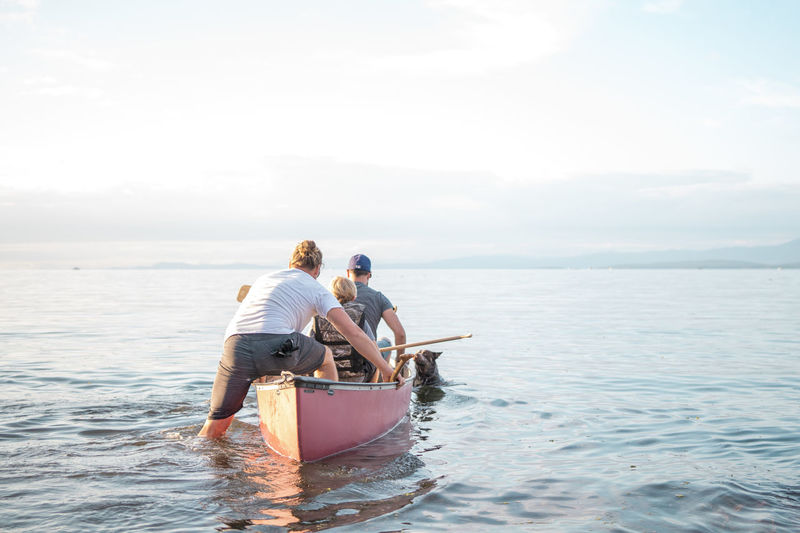 Rear view of parents with son on boat in sea against sky