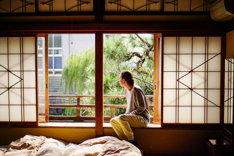 Woman sitting on window sill at home