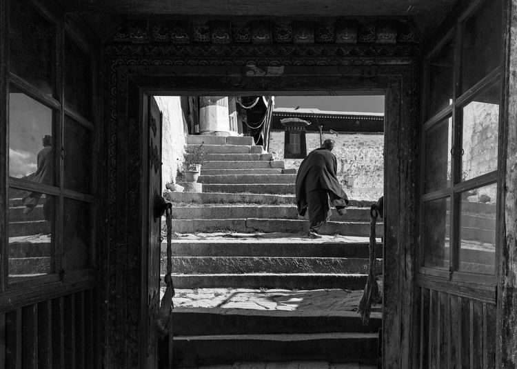 Architecture Staircase Built Structure Full Length Steps And Staircases Rear View One Person Real People Building Indoors  Lifestyles Walking Day Adult Railing Men Architectural Column Window Reflection Monk  Tibet Tibetan Buddhism Travel Blackandwhite