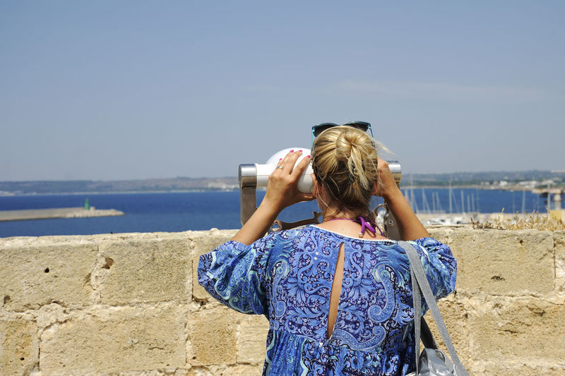 Rear view of woman looking through coin-operated binoculars against sky