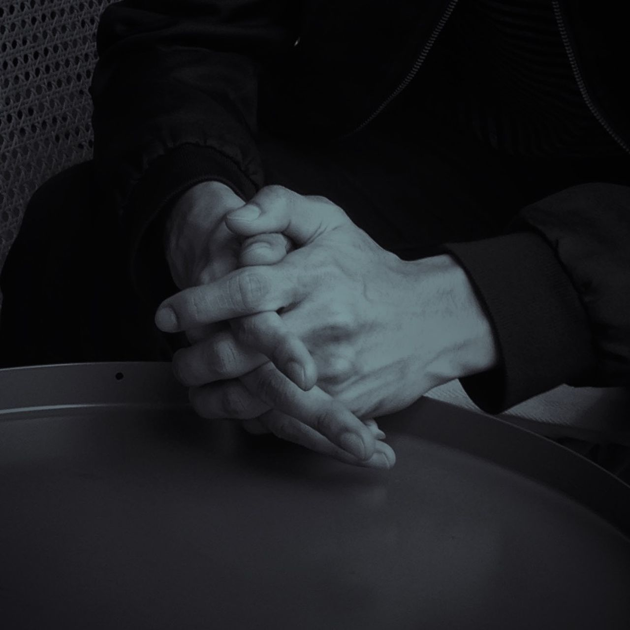 CLOSE-UP OF HANDS HOLDING TABLE