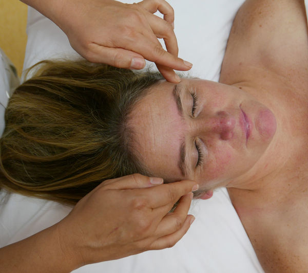High angle view of woman having head massage at spa