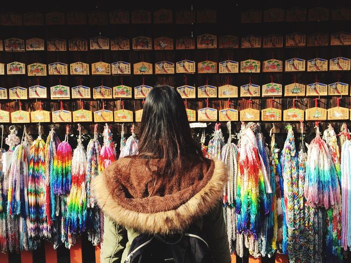 Rear View Of Woman In Fur Coat Standing Against Market Stall