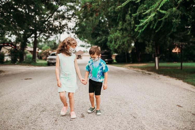 Rear view of friends walking on road along trees