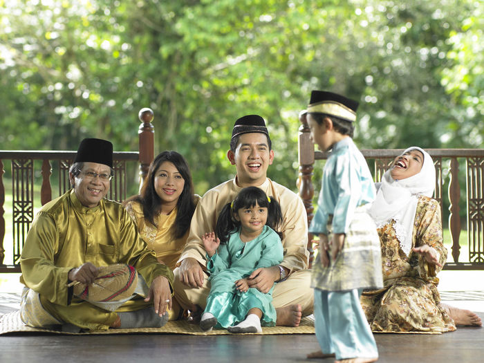 Family sitting in gazebo during traditional festival