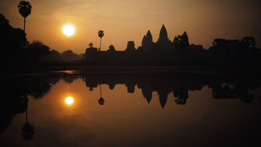 Reflection Of Silhouette Angkor Wat On Calm Lake Against Sky During Sunset
