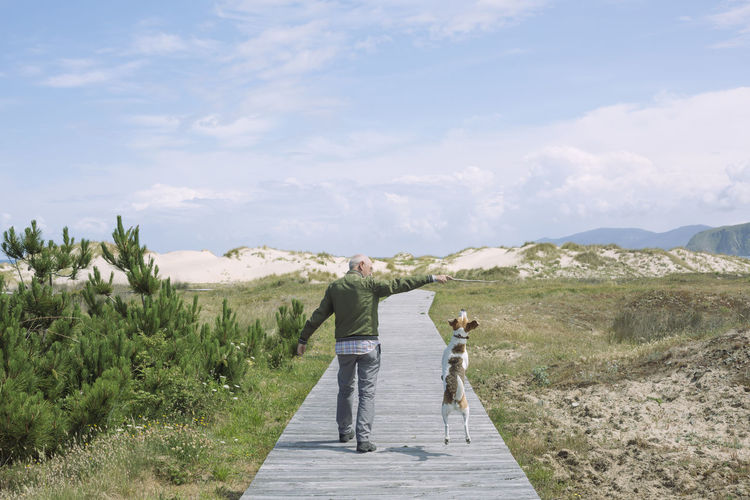 Rear View Of Man Walking With Dog On Boardwalk Against Sky