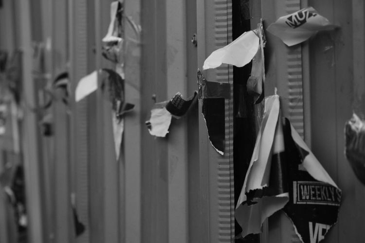 Torn Papers Stuck On Metallic Wall