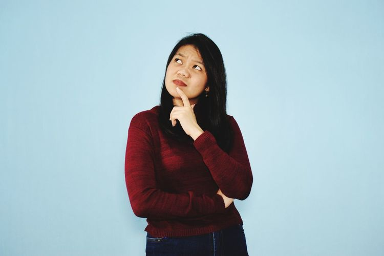 Young woman looking away while standing against gray background