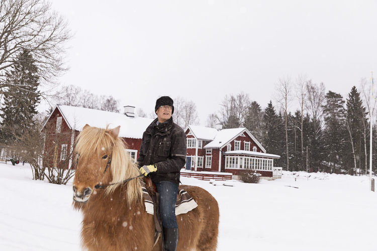 Man with horse standing on snow field
