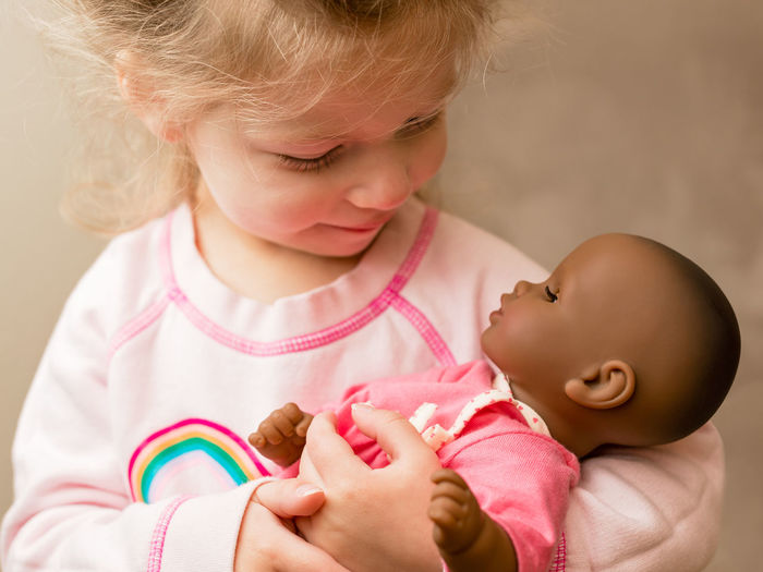 Close-up of cute baby holding girl