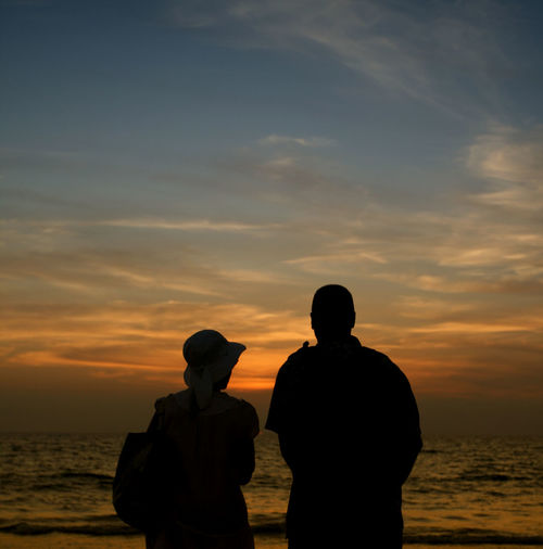 Rear View Of Silhouette Of Couple On Beach Against Sky During Sunset