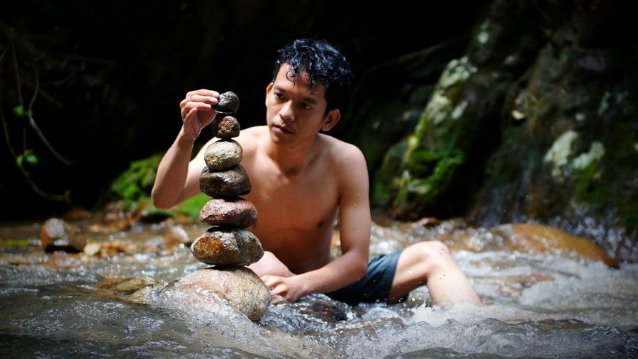 Shirtless young man stacking stone on river
