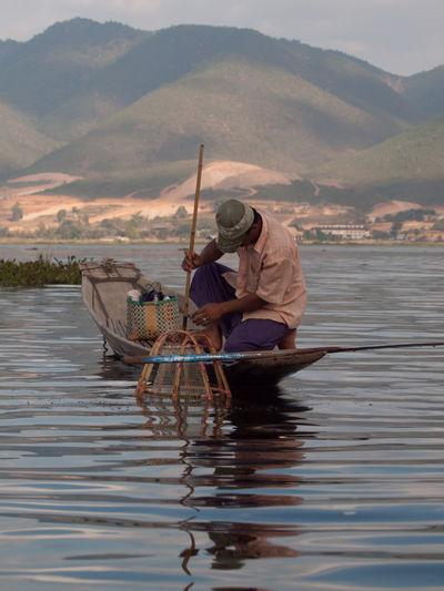 Fisherman fishing on boat in lake