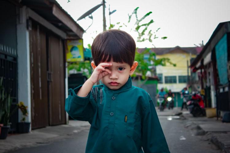 Portrait of boy standing against built structure