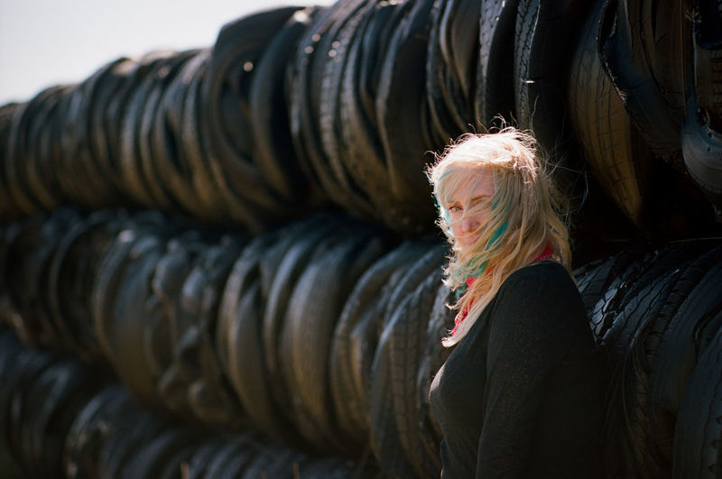 Burn Rubber, Baby One Person Blond Hair Hair Lifestyles Adult Hairstyle Waist Up Portrait Selective Focus Long Hair Dyed Hair Standing Girl Woman Tires Wall Black Rubber Shelter Ranch Farm Wind Breeze Cows Cattle Livestock Plains Prairie Grassland Colorado Eyes Looking At Camera Staring