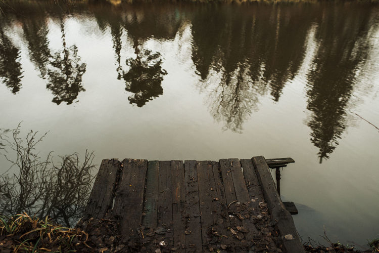 High angle view of wooden post by lake against sky