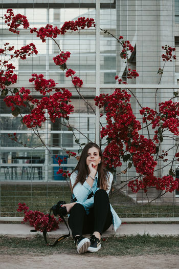 Full length of woman sitting on red flowering plant