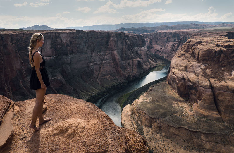 Side view of woman standing on cliff against horseshoe bend