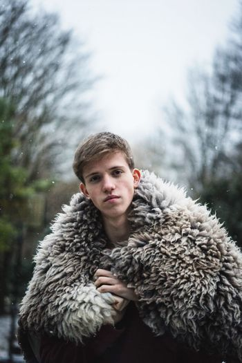 Portrait of young man wearing fur coat during winter