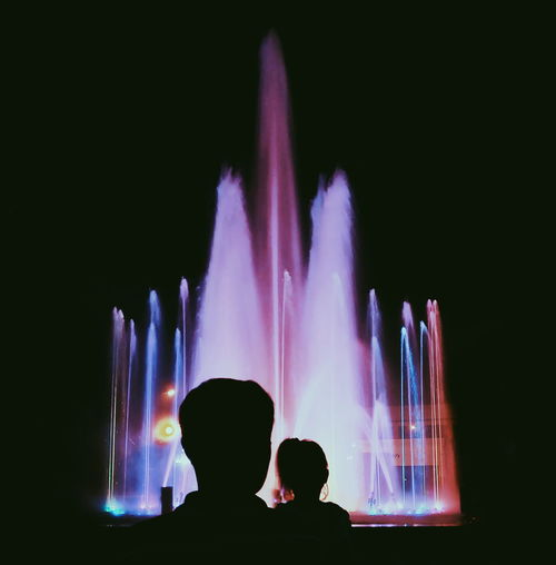Silhouette Man And Woman Against Illuminated Fountain