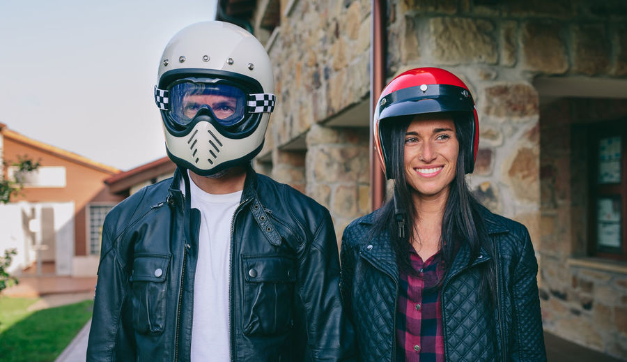 Young couple posing with motorcycle helmets outdoors Horizontal Motorcycle Custom Vintage Bike Cafe Racer Retail  Rider Vehicle Motorbike Biker Motor Transport Caucasian Scrambler Outdoors Nature Tree Green Two People Couple Couple - Relationship Man Male Female Girl Woman Love Leather Jacket Jacket Helmet Protection Plaid Shirt  Portrait Looking At Camera Real People Black Lifestyle Leisure Activity Enjoying Life Happiness Smiling Happy Jeans Togheter Standing Funny Togetherness Glasses Classic
